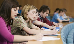 University students take notes in a lecture hall
